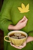 Φλυτζάνι του τσαγιού με το λεμόνι διαθέσιμο, το κίτρινο φύλλο φθινοπώρου Θερμή έννοια ποτών Στοκ φωτογραφίες με δικαίωμα ελεύθερης χρήσης