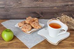 Φλυτζάνι του τσαγιού, της Apple και του σίτου σε ένα ξύλινο υπόβαθρο Στοκ εικόνες με δικαίωμα ελεύθερης χρήσης