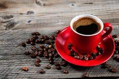 Φλυτζάνι του φρέσκου καφέ με τα φασόλια καφέ στον ξύλινο πίνακα Στοκ Εικόνα