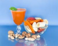 Φλυτζάνι του χυμού καρότων με τους νωπούς καρπούς σε ένα κύπελλο γυαλιού και διεσπαρμένα διάφορα καρύδια Στοκ Φωτογραφίες
