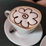 Φλυτζάνι του cappuccino με τη διακόσμηση λουλουδιών στοκ εικόνες