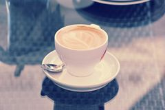 Φλυτζάνι του cappuccino σε ένα πιατάκι με ένα κουταλάκι του γλυκού Στοκ εικόνες με δικαίωμα ελεύθερης χρήσης