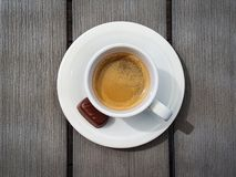 Φλυτζάνι του espresso με τη μικρή πραλίνα σοκολάτας στον αγροτικό γκρίζο πίνακα r στοκ φωτογραφία