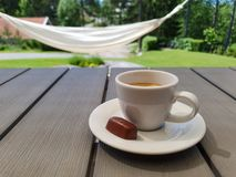 Φλυτζάνι του espresso με τη μικρή πραλίνα σοκολάτας στον γκρίζο πίνακα με την αιώρα και του πράσινου ηλιόλουστου κήπου στο υπόβαθ στοκ φωτογραφία με δικαίωμα ελεύθερης χρήσης