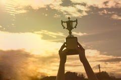 Φλυτζάνι τροπαίων νικητών εκμετάλλευσης χεριών σκιαγραφιών σε ένα πρωτάθλημα στοκ εικόνες με δικαίωμα ελεύθερης χρήσης