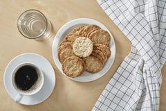 Φλυτζάνι των μαύρων μπισκότων μορίων καφέ, ποτήρι του νερού στο άσπρο πιάτο και ξύλινο υπόβαθρο Τοπ όψη στοκ εικόνες