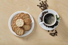 Φλυτζάνι των μαύρων μπισκότων μορίων καφέ στο άσπρο πιάτο και το ξύλινο υπόβαθρο Τοπ όψη στοκ εικόνες