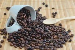 Φλυτζάνι υποβάθρου ποτών με το φασόλι καφέ και την ξύλινη θέση κουταλιών Στοκ εικόνες με δικαίωμα ελεύθερης χρήσης