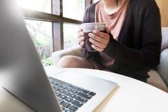 Φλυτζάνι lap-top και καφέ στα χέρια του κοριτσιού που κάθονται στο σπίτι στοκ φωτογραφία με δικαίωμα ελεύθερης χρήσης