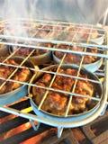 Φλόγα που ψήνει τους μίνι ολισθαίνοντες ρυθμιστές χοιρινού κρέατος στο ράφι ολισθαινόντων ρυθμιστών στη σχάρα στοκ φωτογραφία με δικαίωμα ελεύθερης χρήσης