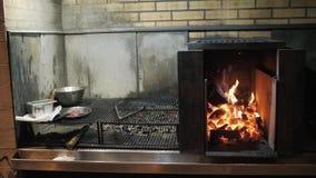Φλόγες και κόκκινη αργεντινή σχάρα χοβόλεων Πυρκαγιά και προετοιμασία σχαρών για τη σχάρα στο εστιατόριο Steakhouse, βόειο κρέας  φιλμ μικρού μήκους