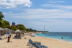 Φοίνικες και ομπρέλες στην παραλία Playa Ancon κοντά στο Τρινιδάδ στοκ φωτογραφία