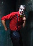 Φοβερός κλόουν και θέμα αποκριών: Τρελλός κόκκινος κλόουν σε ένα πουκάμισο με suspenders Στοκ φωτογραφία με δικαίωμα ελεύθερης χρήσης