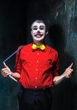 Φοβερός κλόουν και θέμα αποκριών: Τρελλός κόκκινος κλόουν σε ένα πουκάμισο με suspenders Στοκ Φωτογραφίες