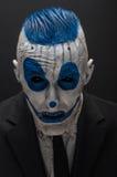 Φοβερός κλόουν και θέμα αποκριών: Τρελλός μπλε κλόουν στο μαύρο κοστούμι που απομονώνεται σε ένα σκοτεινό υπόβαθρο στο στούντιο Στοκ Φωτογραφίες