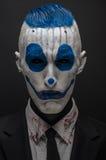Φοβερός κλόουν και θέμα αποκριών: Τρελλός μπλε κλόουν στο μαύρο κοστούμι που απομονώνεται σε ένα σκοτεινό υπόβαθρο στο στούντιο Στοκ Εικόνες