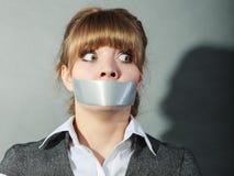 Φοβησμένη γυναίκα με το στόμα που δένεται με ταινία κλεισμένο λογοκρισία στοκ εικόνες