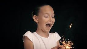 Φοβησμένη εκμετάλλευση κοριτσιών στα χέρια που καίνε sparkler με τους καυτούς σπινθήρες στο μαύρο υπόβαθρο φιλμ μικρού μήκους