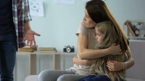 Φοβησμένη μητέρα και λίγη κόρη που αγκαλιάζουν και που προστατεύουν από το σκληρό πατέρα φιλμ μικρού μήκους