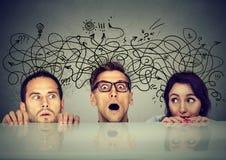 Φοβησμένοι άνθρωποι που ανταλλάσσουν τη διαφορετική σκέψη μεριδίου που κρυφοκοιτάζει από κάτω από τον πίνακα Στοκ εικόνα με δικαίωμα ελεύθερης χρήσης