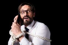 Φοβησμένος μέσος ηλικίας επιχειρηματίας που δένεται με το σχοινί που μιλά στο smartphone Στοκ Εικόνα