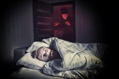 Φοβησμένο αγόρι που βρίσκεται στο κρεβάτι ενώ ο καλυμμένος ξένος Στοκ φωτογραφία με δικαίωμα ελεύθερης χρήσης