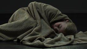 Φοβησμένο κορίτσι που υποχωρεί από το φόβο, που βρίσκεται στο πάτωμα και που καλύπτει το κεφάλι με το κάλυμμα φιλμ μικρού μήκους