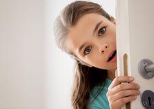 Φοβησμένο όμορφο κρύψιμο κοριτσιών πίσω από την πόρτα στο σπίτι στοκ φωτογραφίες με δικαίωμα ελεύθερης χρήσης