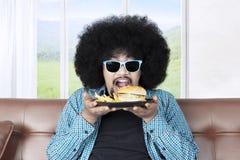 Φοβιτσιάρες cheeseburger εκμετάλλευσης τύπων στον καναπέ Στοκ φωτογραφίες με δικαίωμα ελεύθερης χρήσης