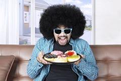 Φοβιτσιάρης τύπος με τα εύγευστα donuts Στοκ φωτογραφία με δικαίωμα ελεύθερης χρήσης