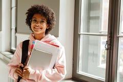 Φοιτητής πανεπιστημίου με τα βιβλία που στέκονται στο εσωτερικό Στοκ φωτογραφία με δικαίωμα ελεύθερης χρήσης
