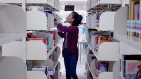 Φοιτητής πανεπιστημίου που ψάχνει το βιβλίο στη βιβλιοθήκη απόθεμα βίντεο