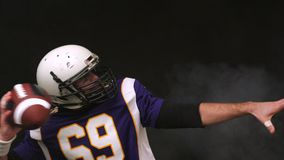 Φορέας αμερικανικού ποδοσφαίρου που παίρνει έτοιμος να ρίξει τη σφαίρα, κινηματογράφηση σε πρώτο πλάνο, μαύρο υπόβαθρο φιλμ μικρού μήκους