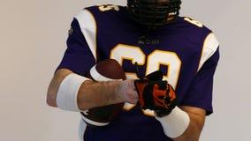 Φορέας αμερικανικού ποδοσφαίρου που φορά το αθλητικό φόρεμά του στο μαύρο υπόβαθρο φιλμ μικρού μήκους