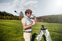 Φορέας γκολφ που κρατά ένα γκολφ κλαμπ στο γήπεδο του γκολφ στοκ εικόνα