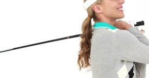 Φορέας γκολφ που χτυπά τη σφαίρα και που χαμογελά στη κάμερα απόθεμα βίντεο