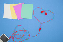 φορέας μουσικής και κόκκινο ακουστικό στο μπλε υπόβαθρο εγγράφου, βαλεντίνος Στοκ φωτογραφία με δικαίωμα ελεύθερης χρήσης