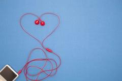 φορέας μουσικής και κόκκινο ακουστικό στο μπλε υπόβαθρο εγγράφου, βαλεντίνος Στοκ Εικόνες