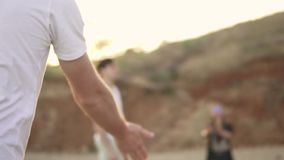 Φορέας πετοσφαίρισης που κλωτσά μια σφαίρα Χαρούμενοι νέοι φίλοι που παίζουν volley τη σφαίρα στην παραλία θαλασσίως το βράδυ φιλμ μικρού μήκους