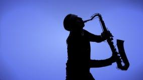 Φορέας Saxophone σε ένα υπόβαθρο χρώματος φιλμ μικρού μήκους