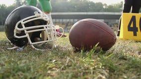 Φορείς αμερικανικού ποδοσφαίρου που εκπαιδεύουν μια ηλιόλουστη ημέρα, την κινηματογράφηση σε πρώτο πλάνο του κράνους και τη σφαίρ απόθεμα βίντεο