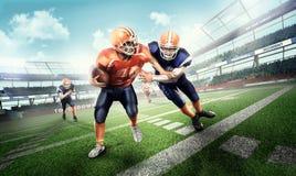 Φορείς αμερικανικού ποδοσφαίρου επιθετικότητας στη χλόη στο στάδιο Στοκ Φωτογραφία