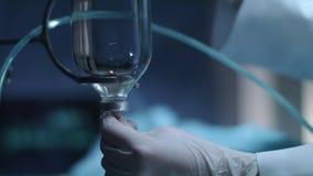 Φορημένη γάντια τεθειμένη χέρι βελόνα στο μετρητή πτώσης Μπουκάλι χημειοθεραπείας φιλμ μικρού μήκους
