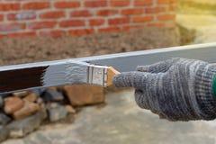 Φορημένος γάντια εγχυτήρας ζωγραφικής χεριών αντιοξειδωτικός στους πόλους χάλυβα για την κατασκευή στοκ εικόνες