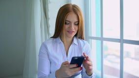 Φορητή συσκευή χρήσης νέων κοριτσιών για τα κοινωνικά δίκτυα ξεφυλλίσματος το πρότυπο της δεκαετίας του '20 επικοινωνεί on-line α απόθεμα βίντεο
