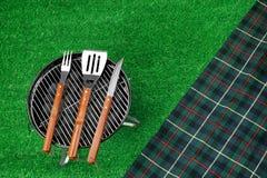 Φορητή σχάρα σχαρών στο χορτοτάπητα, τα εργαλεία σχαρών και το κάλυμμα Στοκ Φωτογραφία