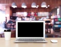 Φορητός προσωπικός υπολογιστής σε ένα ξύλινο γραφείο με τη καφετερία Στοκ φωτογραφίες με δικαίωμα ελεύθερης χρήσης