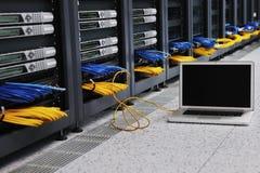 Φορητός προσωπικός υπολογιστής στο δωμάτιο δικτύων κεντρικών υπολογιστών Στοκ εικόνα με δικαίωμα ελεύθερης χρήσης