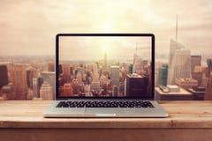 Φορητός προσωπικός υπολογιστής πέρα από τον ορίζοντα πόλεων της Νέας Υόρκης Αναδρομική επίδραση φίλτρων Στοκ Εικόνες