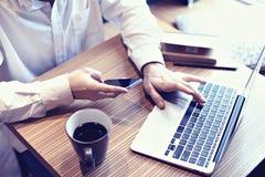 Φορητός προσωπικός υπολογιστής χρήσης επιχειρησιακών ατόμων λογιστικής και κινητό τηλέφωνο στον καφέ, επιχειρηματικό σχέδιο γραψί Στοκ Εικόνες